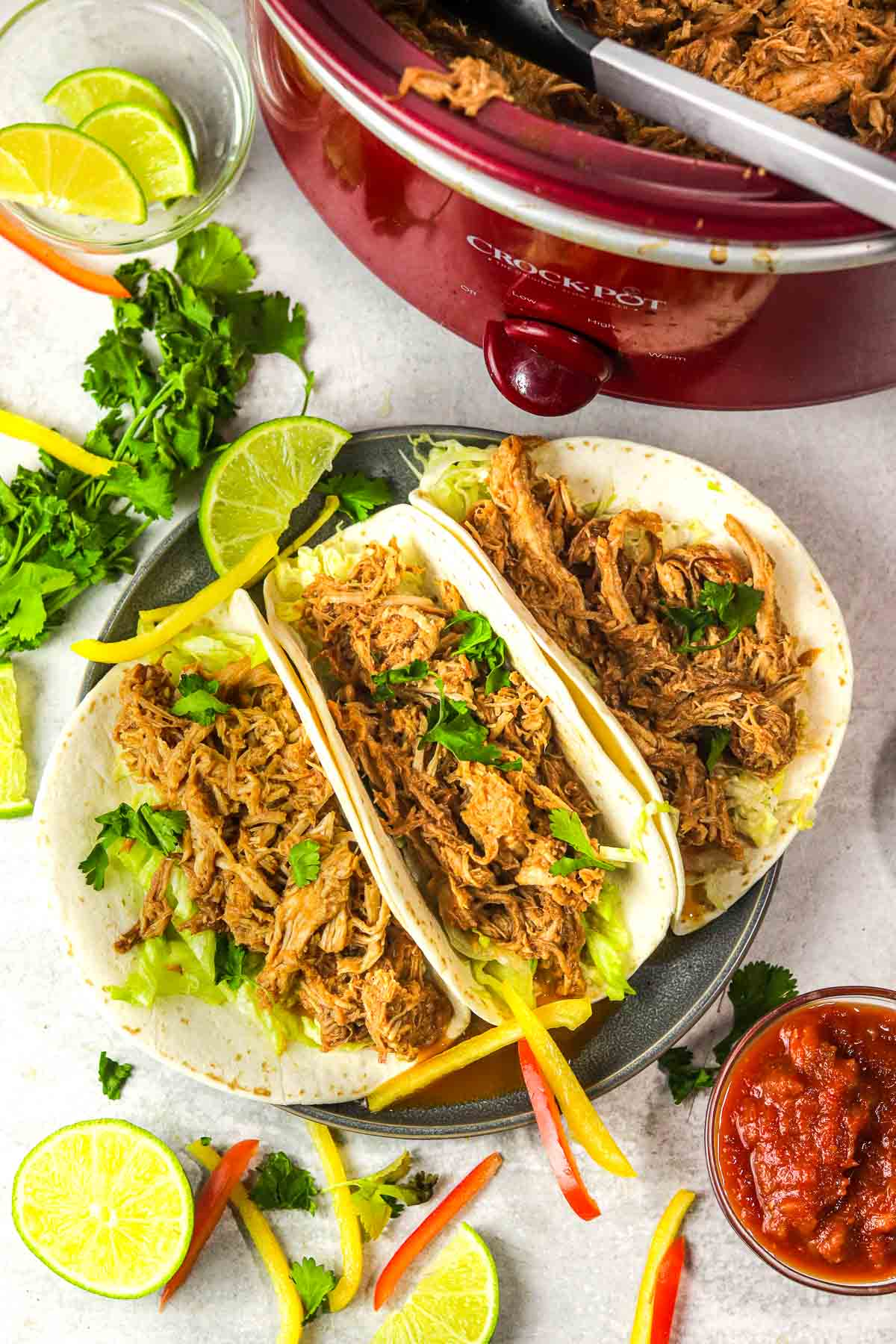 Plate of slow cooker pork barbacoa with cilantro, lime and peppers.
