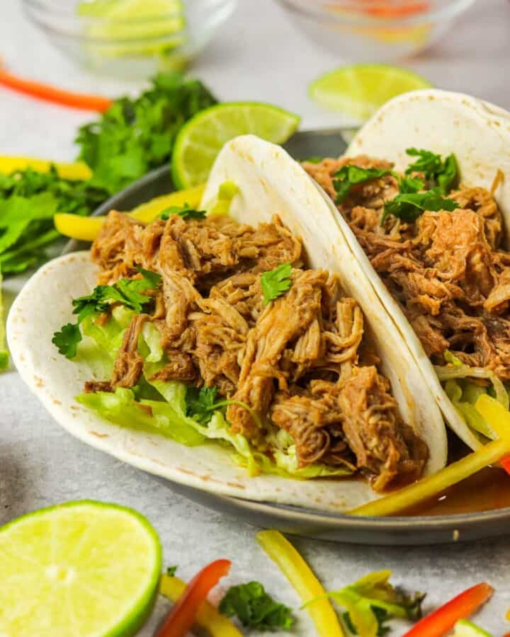 Slow cooker Pork Barbacoa tacos with cilantro and peppers.