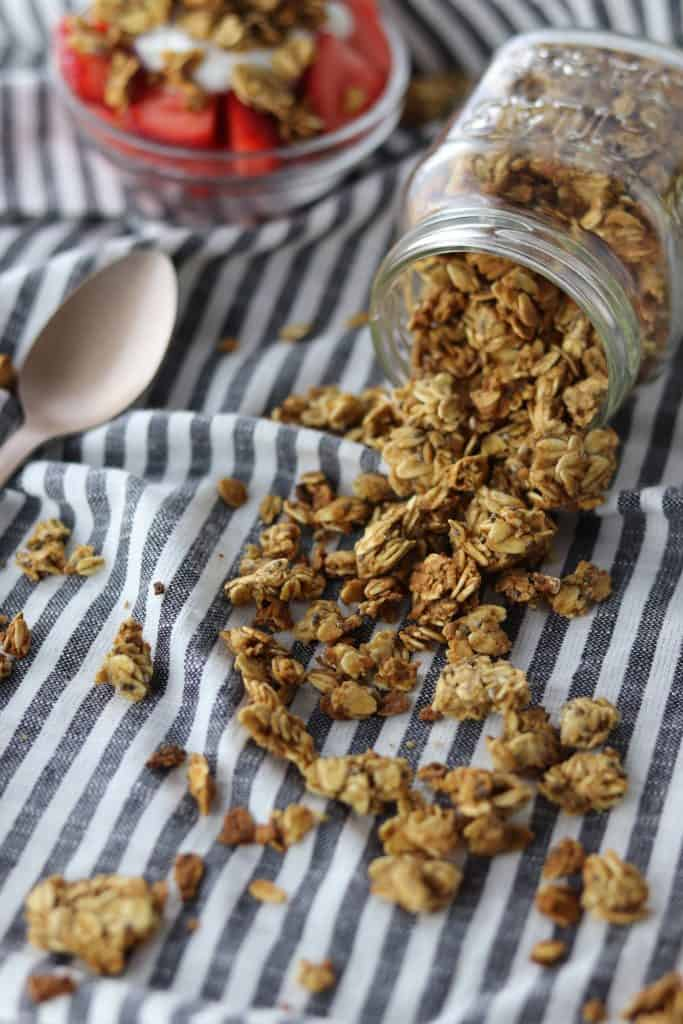 chia & flax granola pouring from jar with parfait