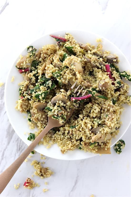swiss chard and mushroom quinoa on marble counter