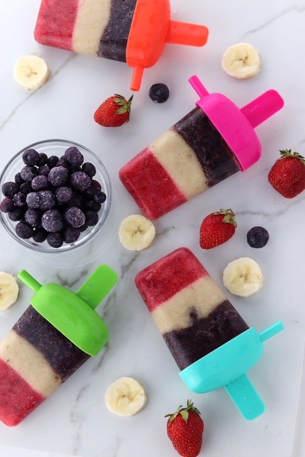 red white and blue fruit pops with blueberries banana and strawberries on counter