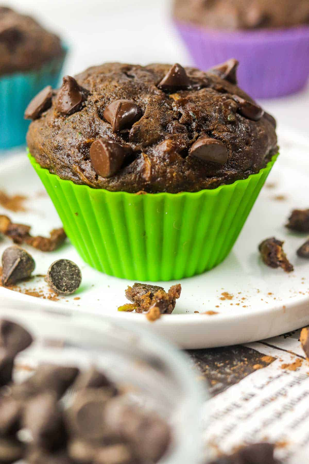 chocolate zucchini banana muffin in a green muffin liner on a plate.
