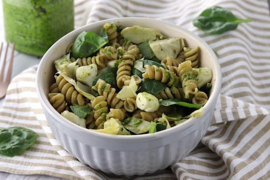 Spinach and artichoke whole wheat pesto pasta salad in a bowl on a napkin