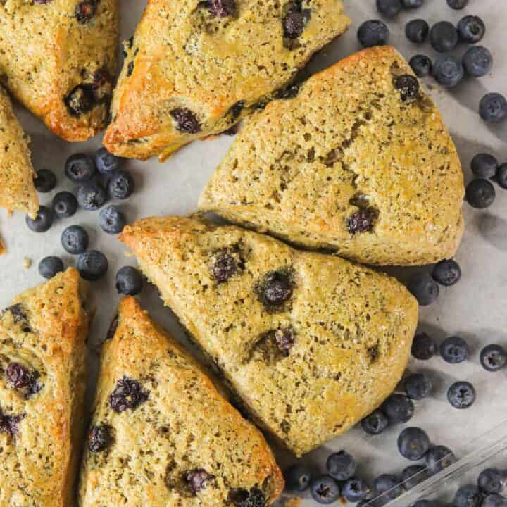 Up close whole wheat blueberry yogurt scones surrounded by blueberries