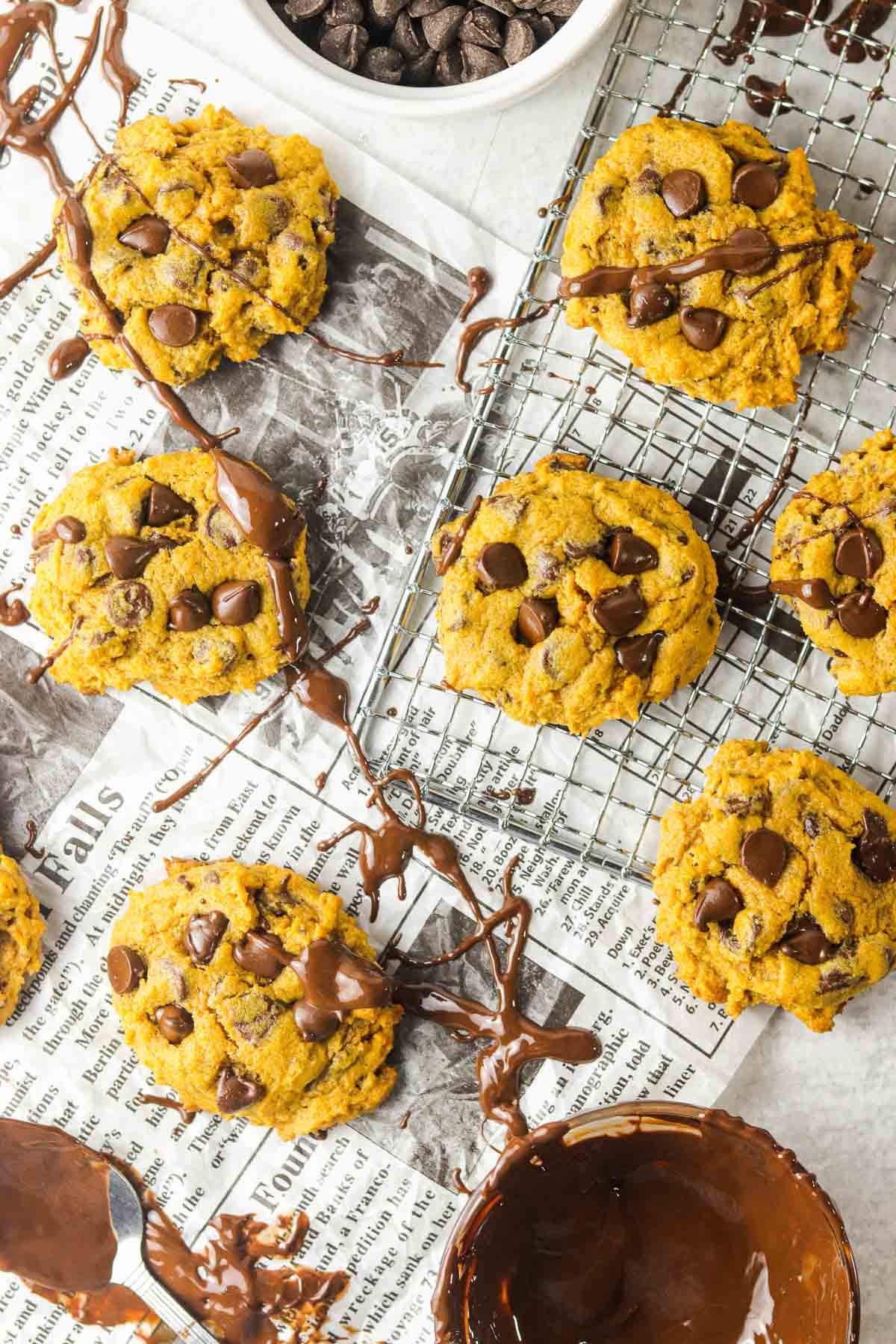 chocolate chip pumpkin cookies on newspaper with drizzled chocolate.