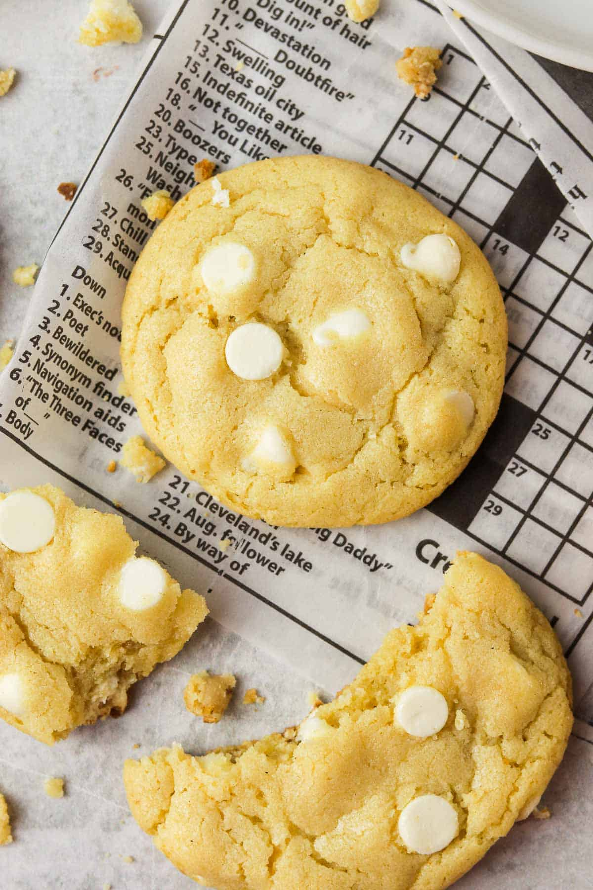 Double white chocolate chip cookie on newspaper.