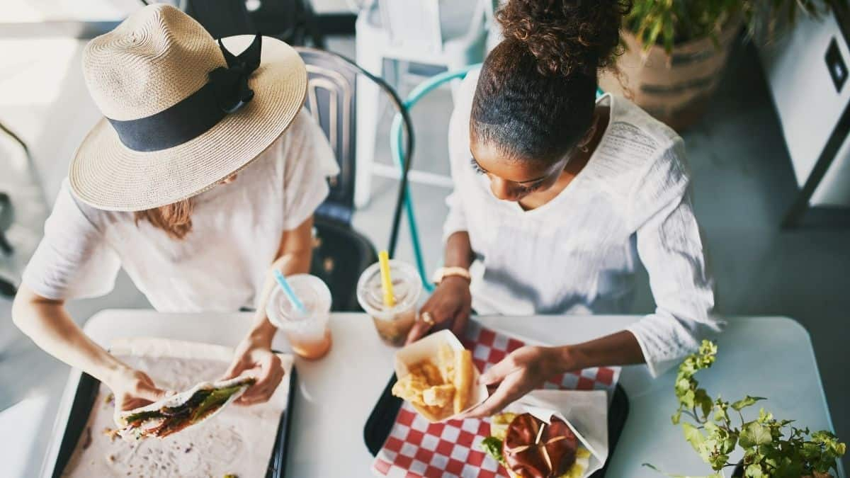 two women talking over lunch enjoying a burger and fries and a wrap.