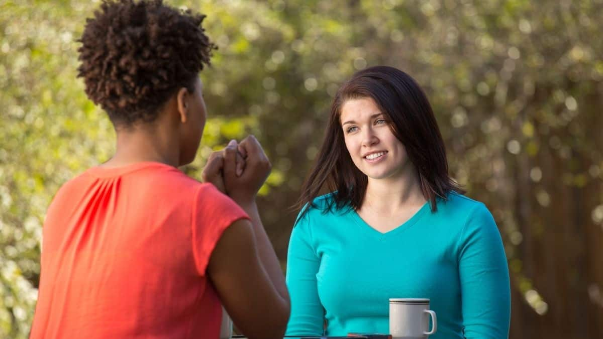 two women talking with eachother outside over coffee.