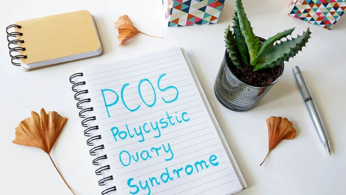 PCOS polysistic ovary syndrome written in a journal with blue marker.
