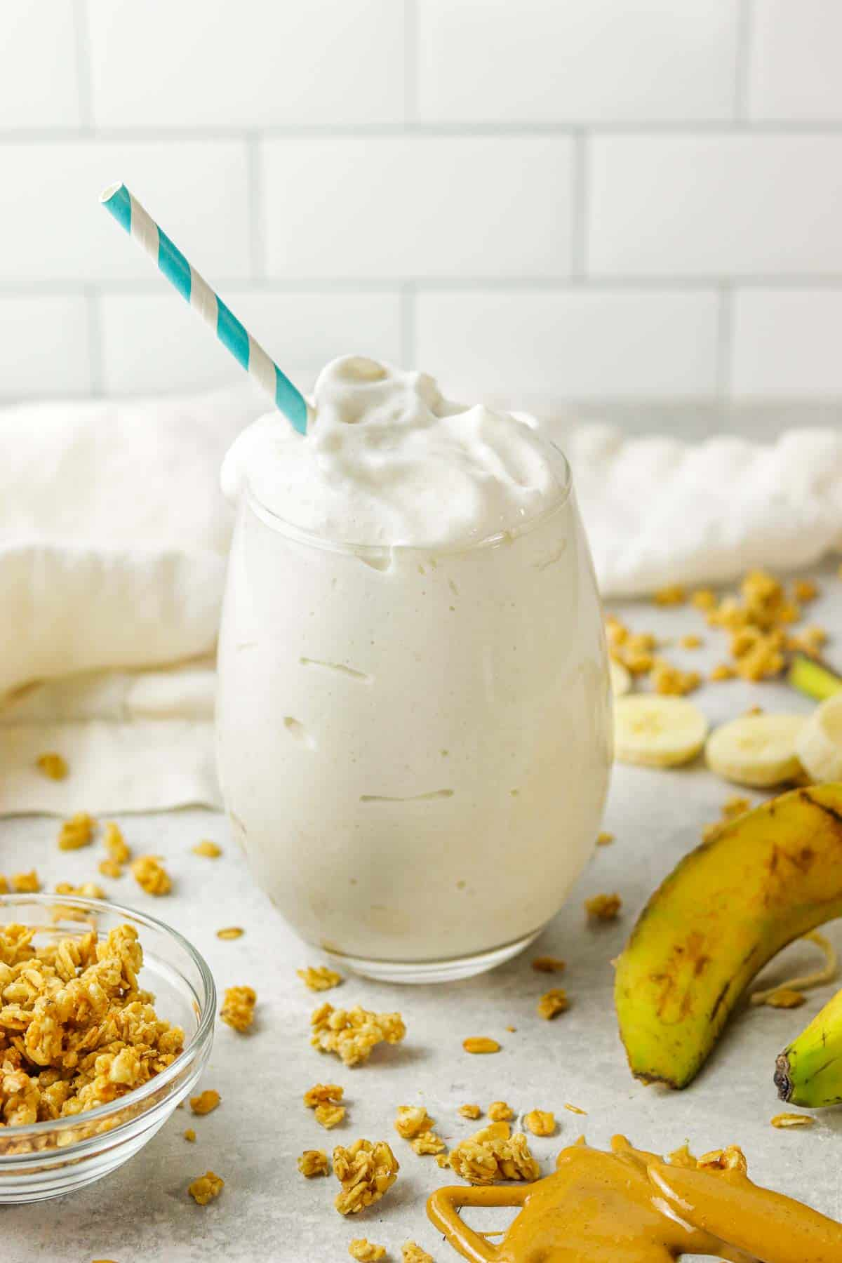 A banana protein shake on the counter with granola around it