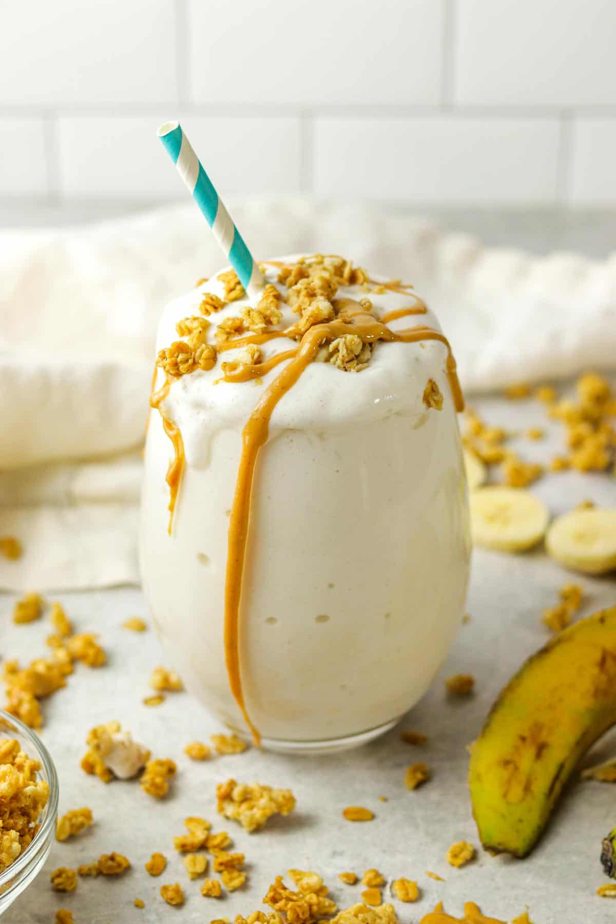A banana protein shake with granola and peanut butter on it