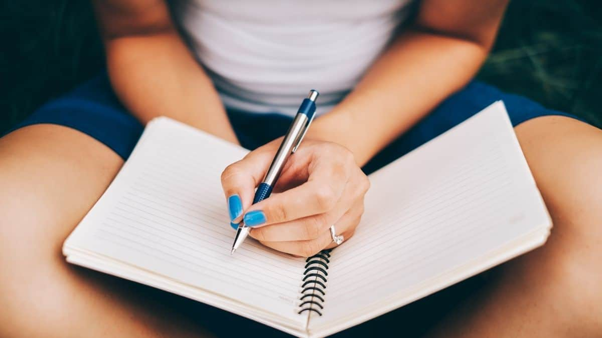 A woman sitting criss-cross writing in her journal.