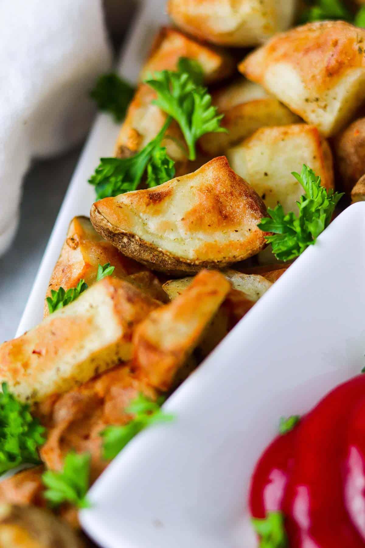 Up close air fryer potatoes on a white platter.