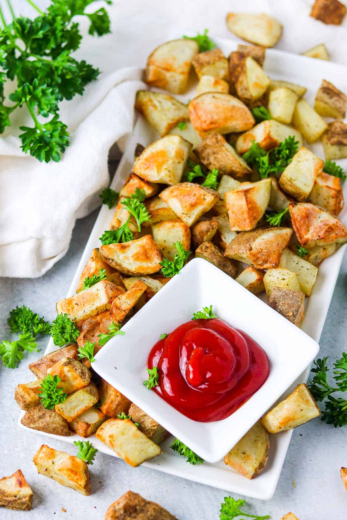 air fryer potatoes on a plate with ketchuop.