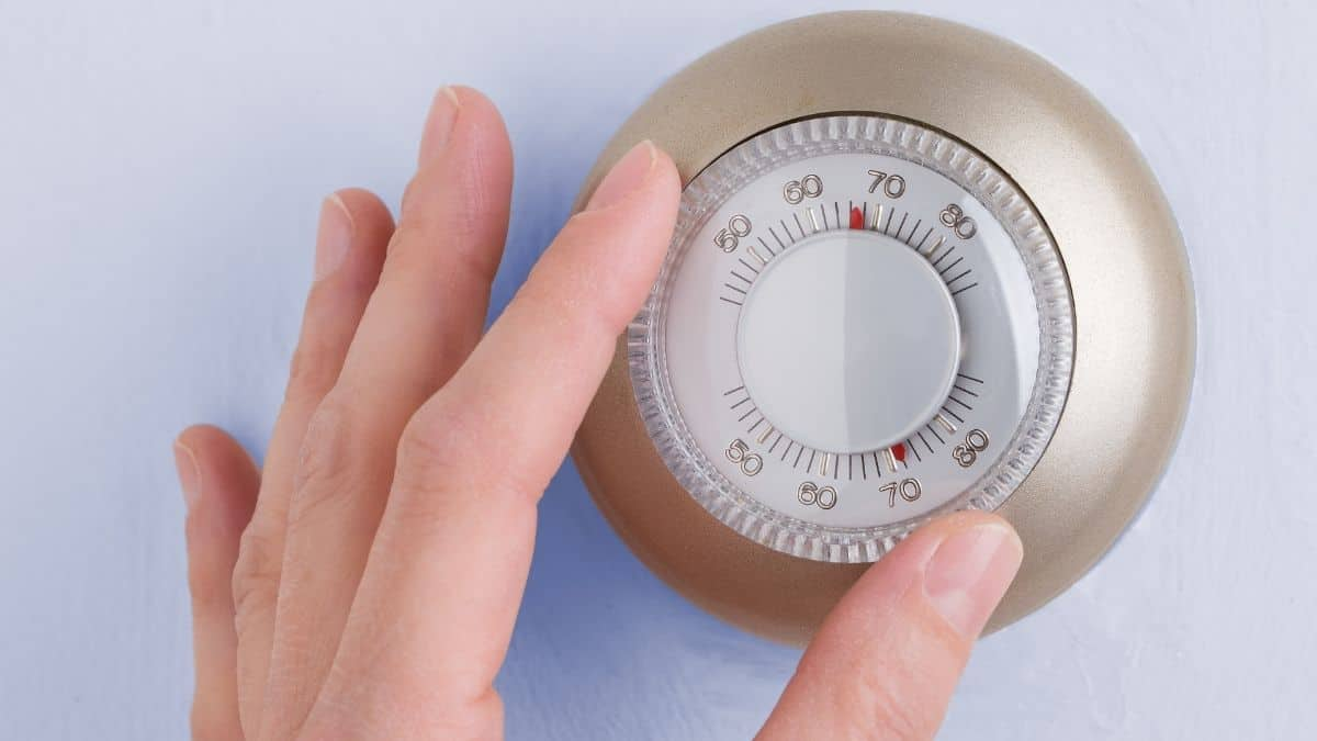 A hand changing the temperature on a thermostat
