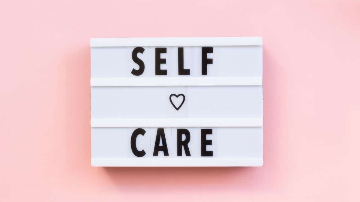 White sign with the words self care spelled out on a pick background