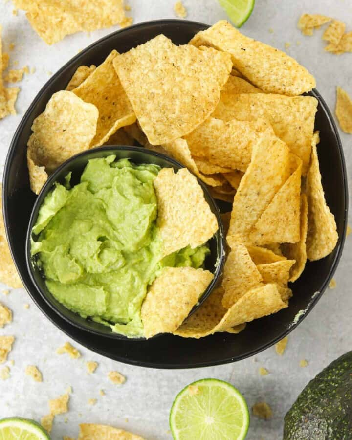 A bowl of avocado lime crema with tortillas chips.