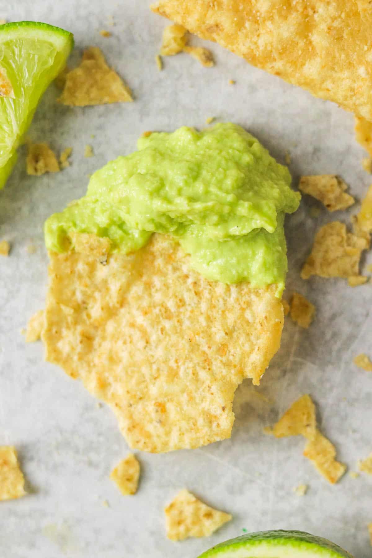 A tortilla chip dipped into avocado lime crema.
