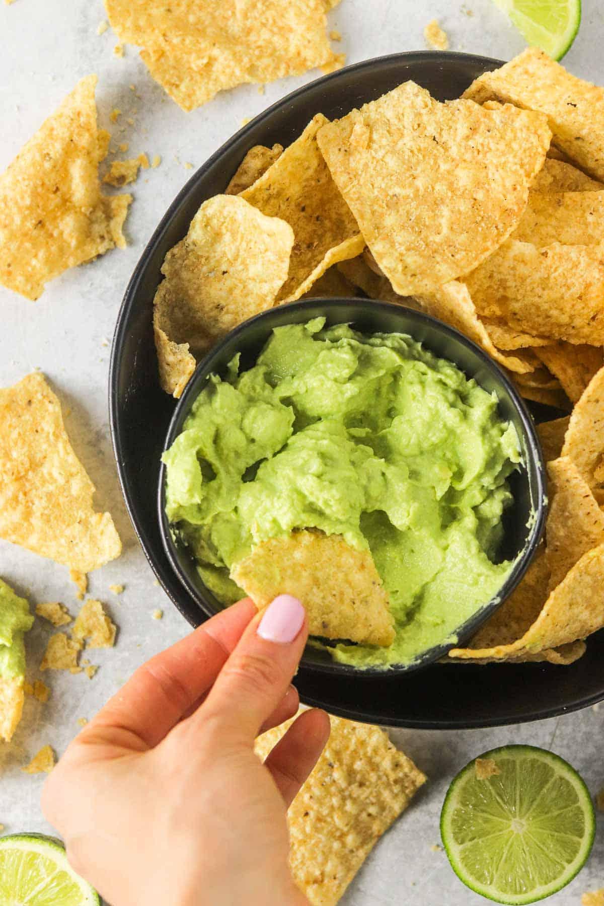 Dipping a chip into a bowl of avocado lime crema