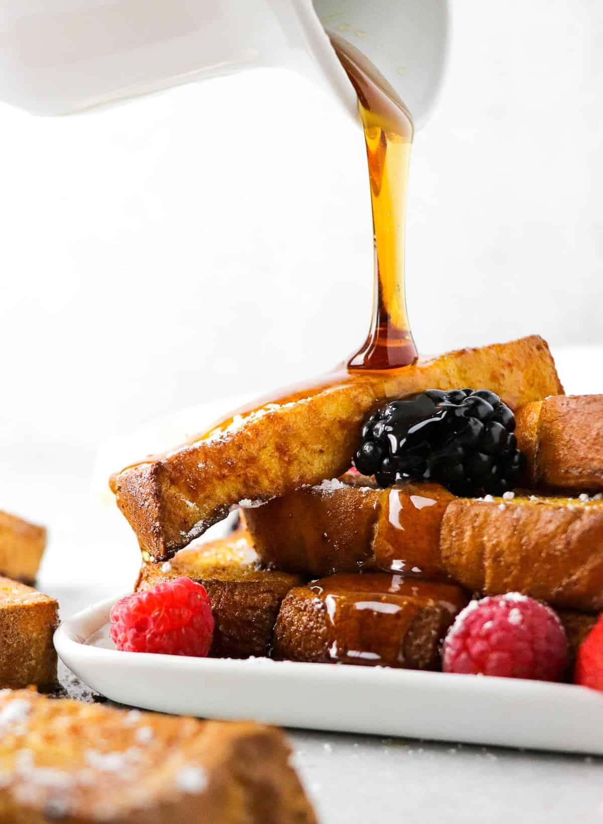 Pouring maple syrup on a plate of air fryer french toast sticks.