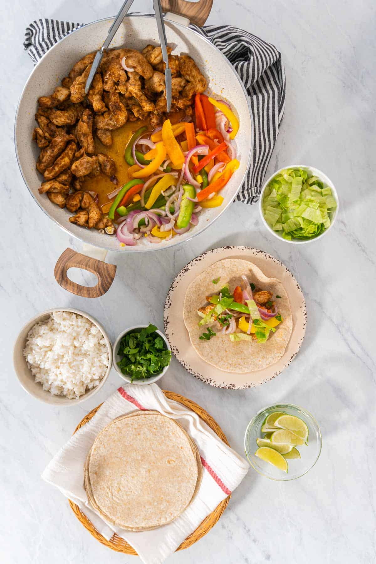 Assembling chicken fajita tacos with lettuce and limes.