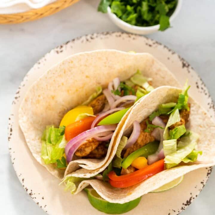 Two chicken fajita tacos on a plate with a bowl of cilantro.