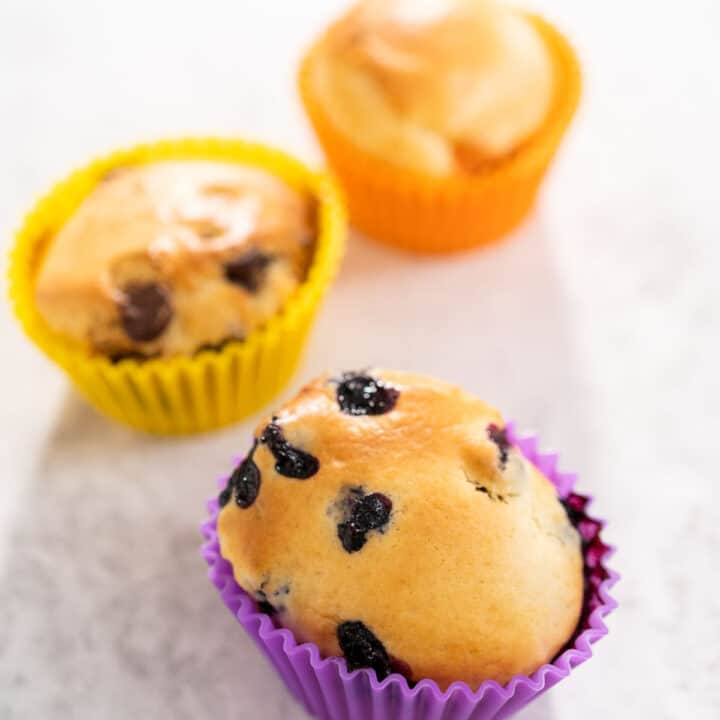 fruit, veggie and chocolate air fryer muffins sitting on the counter in colorful molds.