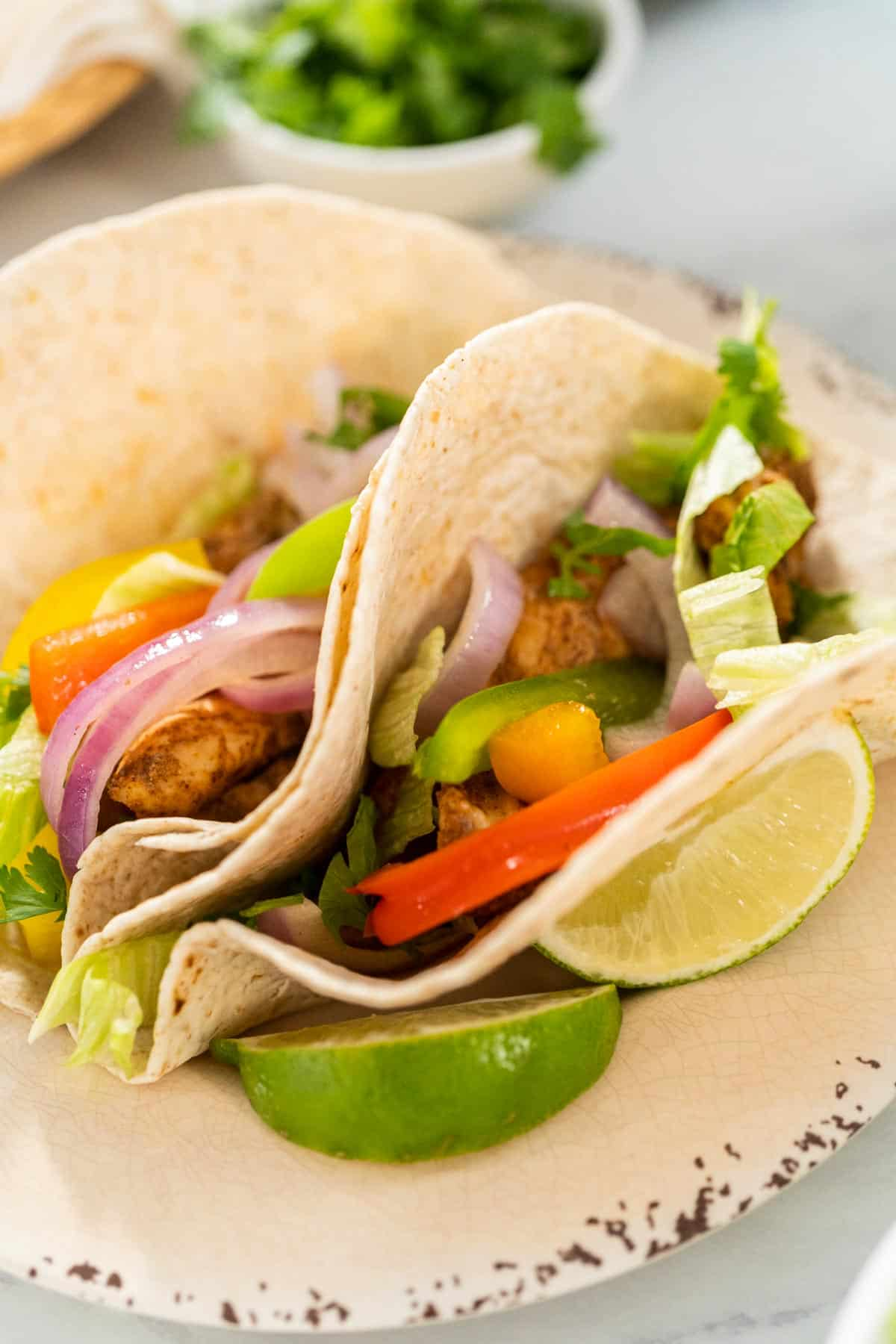 two finished chicken fajita tacos on a plate with cilantro