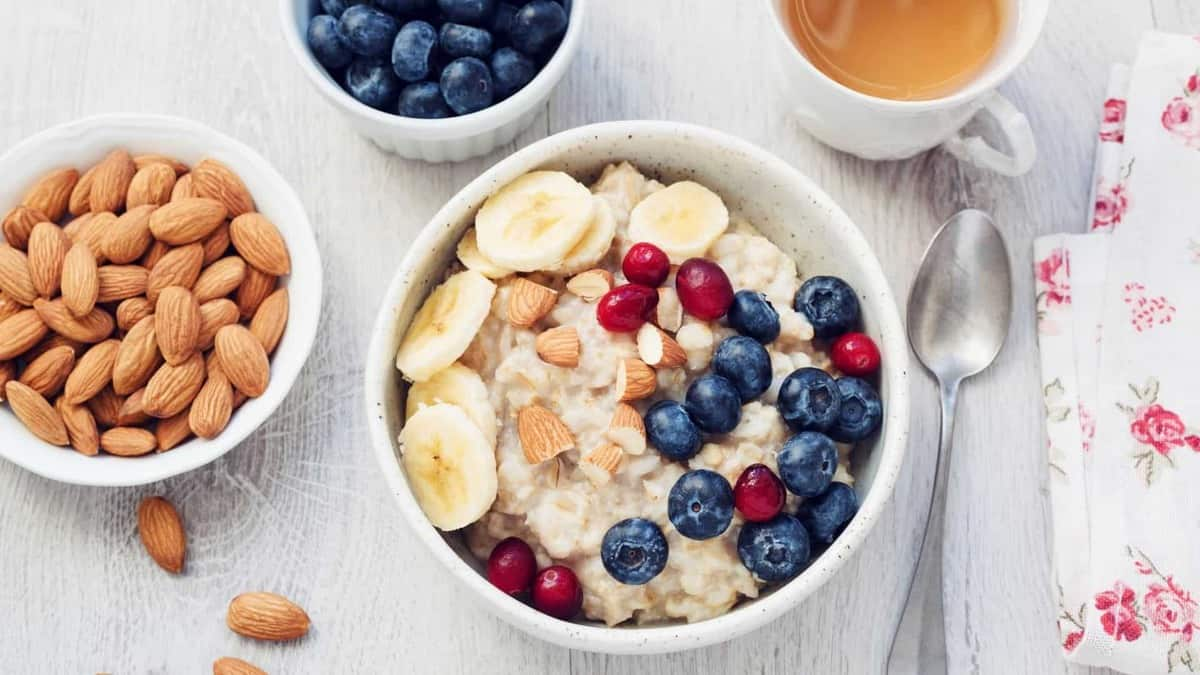 A bowl of oatmeal on a table with berries and nuts.