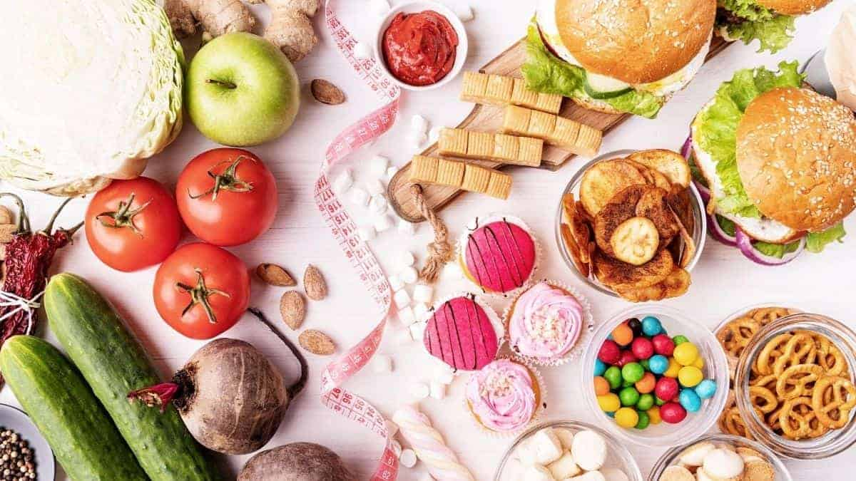 healthy and unhealthy foods together on a pink background.