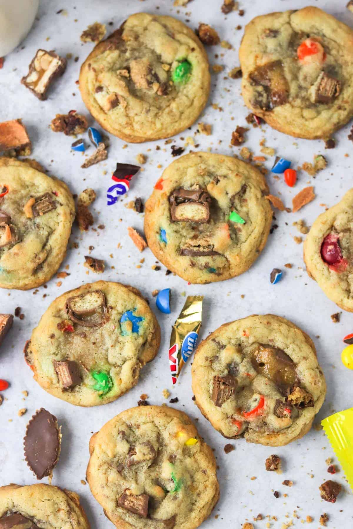 A close up of many candy cookies on the counter with candy pieces around them.