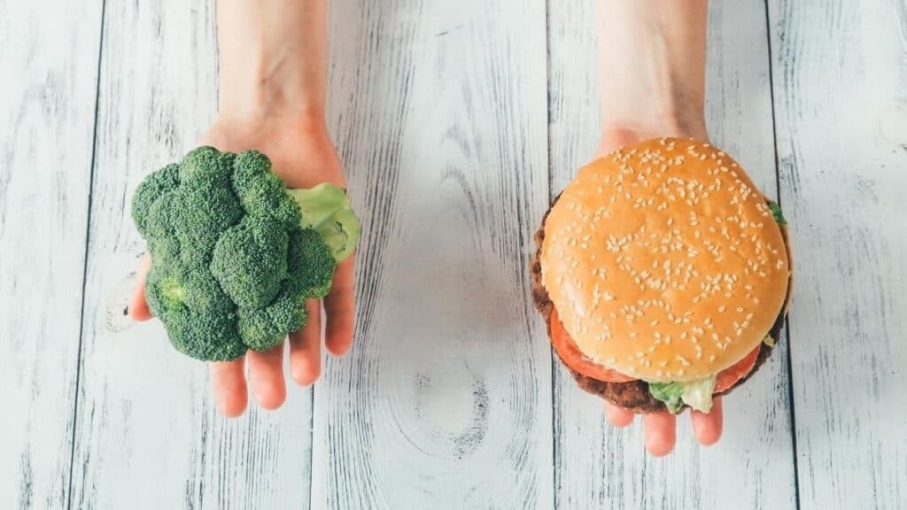 holding broccoli and holding and apple for flexible dieting