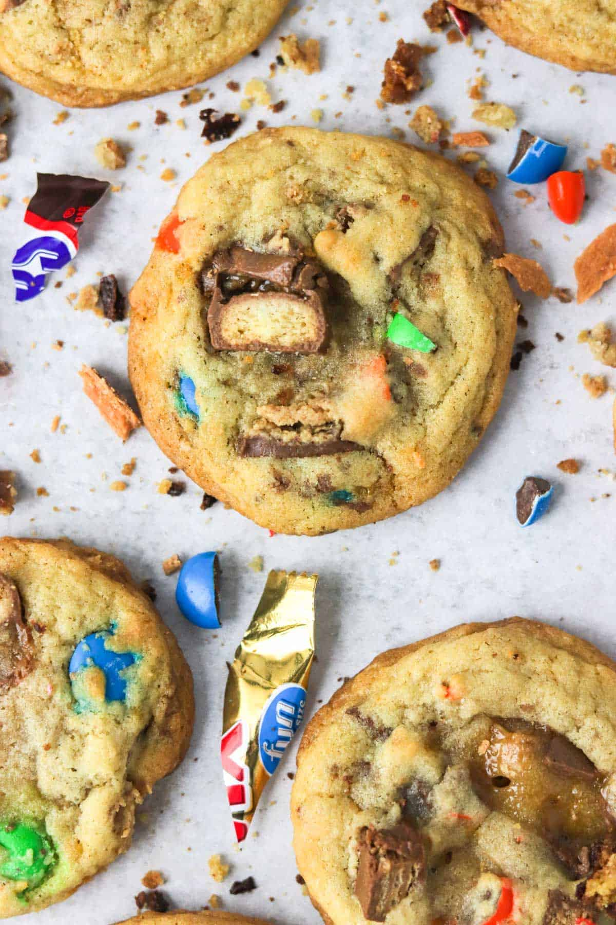 A close up of candy bar cookies with candy pieces around them.