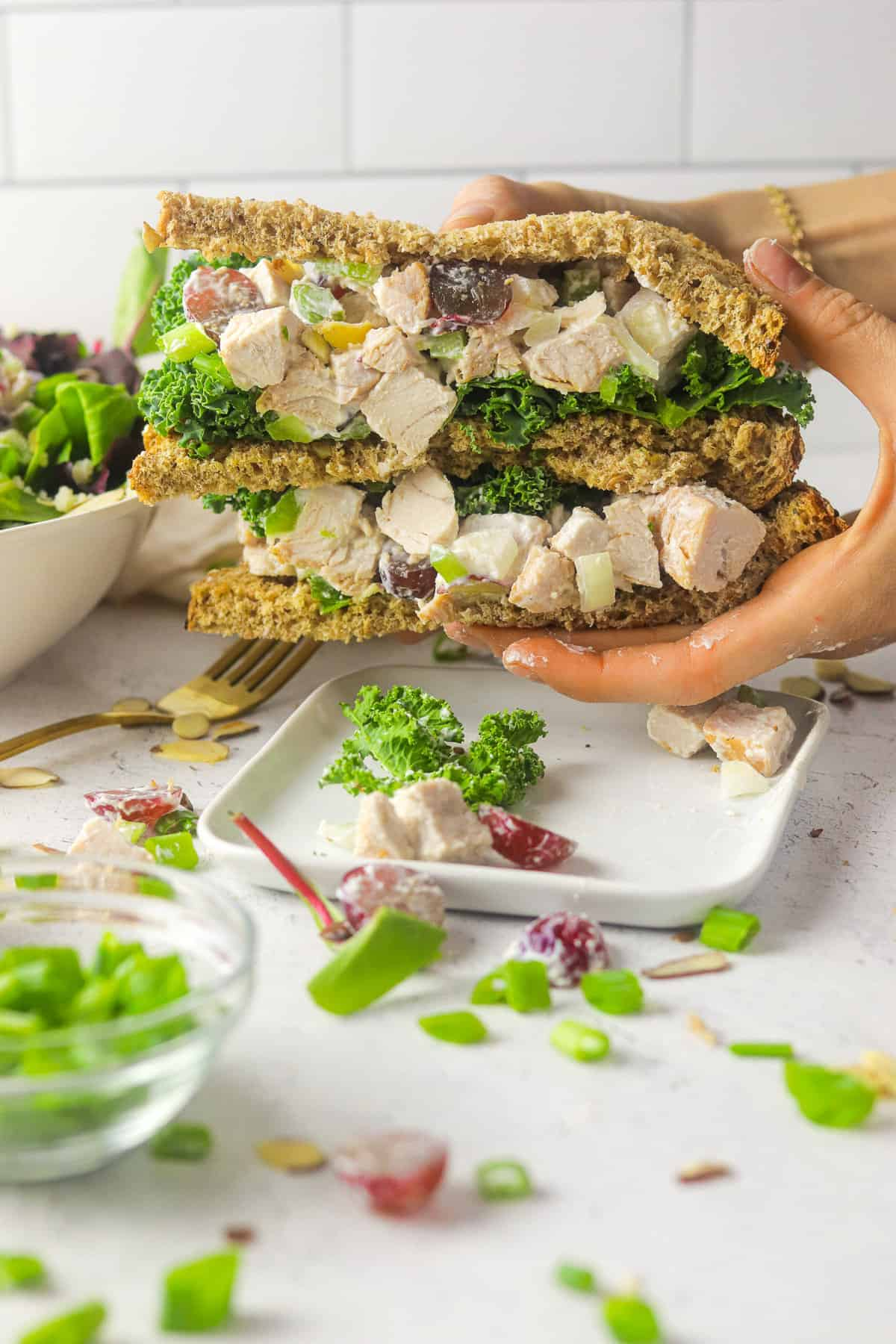 holding turkey salad with grapes sandwich.