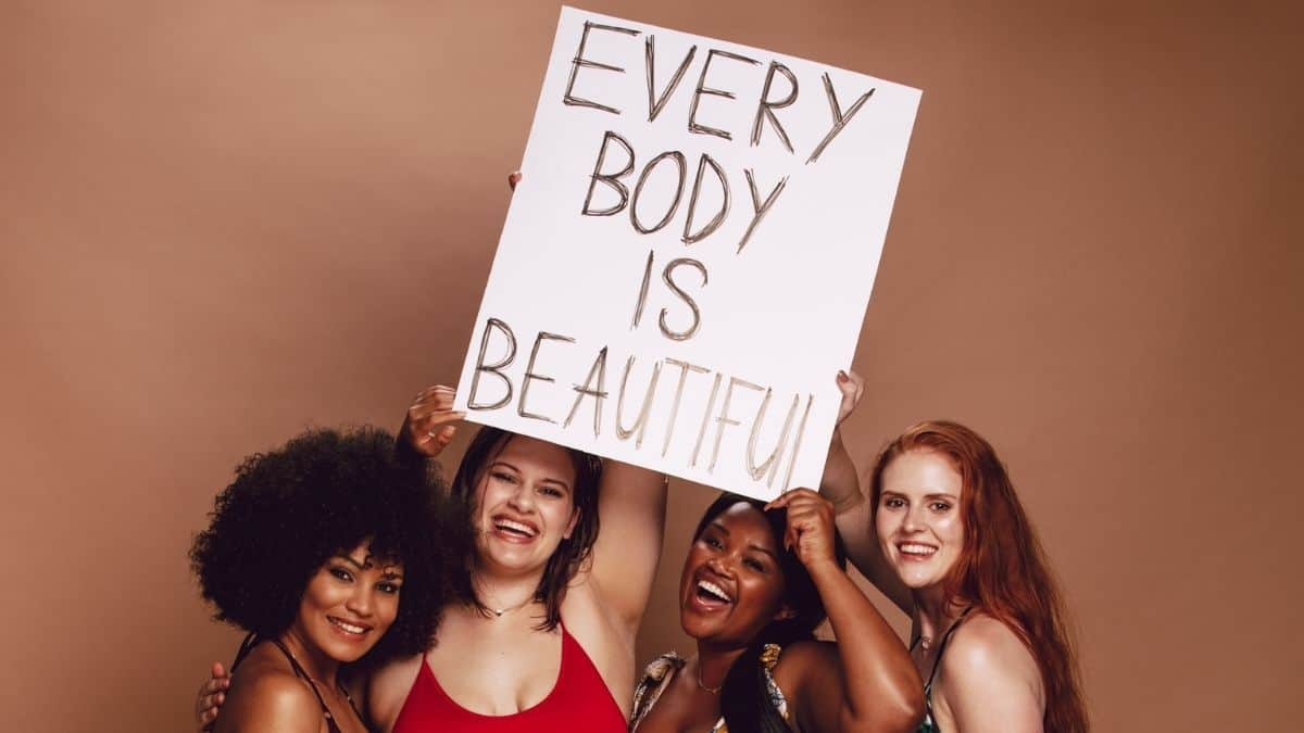 Women holding the sign saying every body is beautiful.