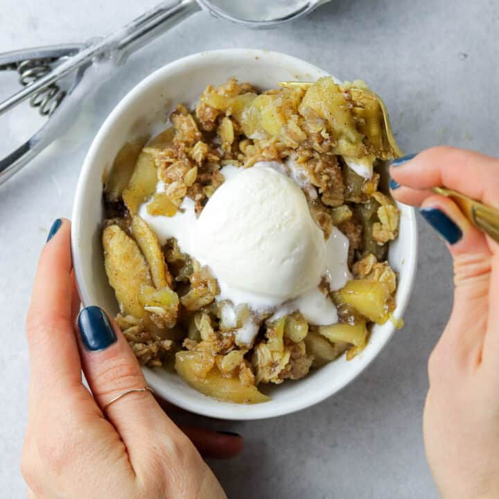 Two hands holding bowl of skillet apple crisp with ice cream and eating it.