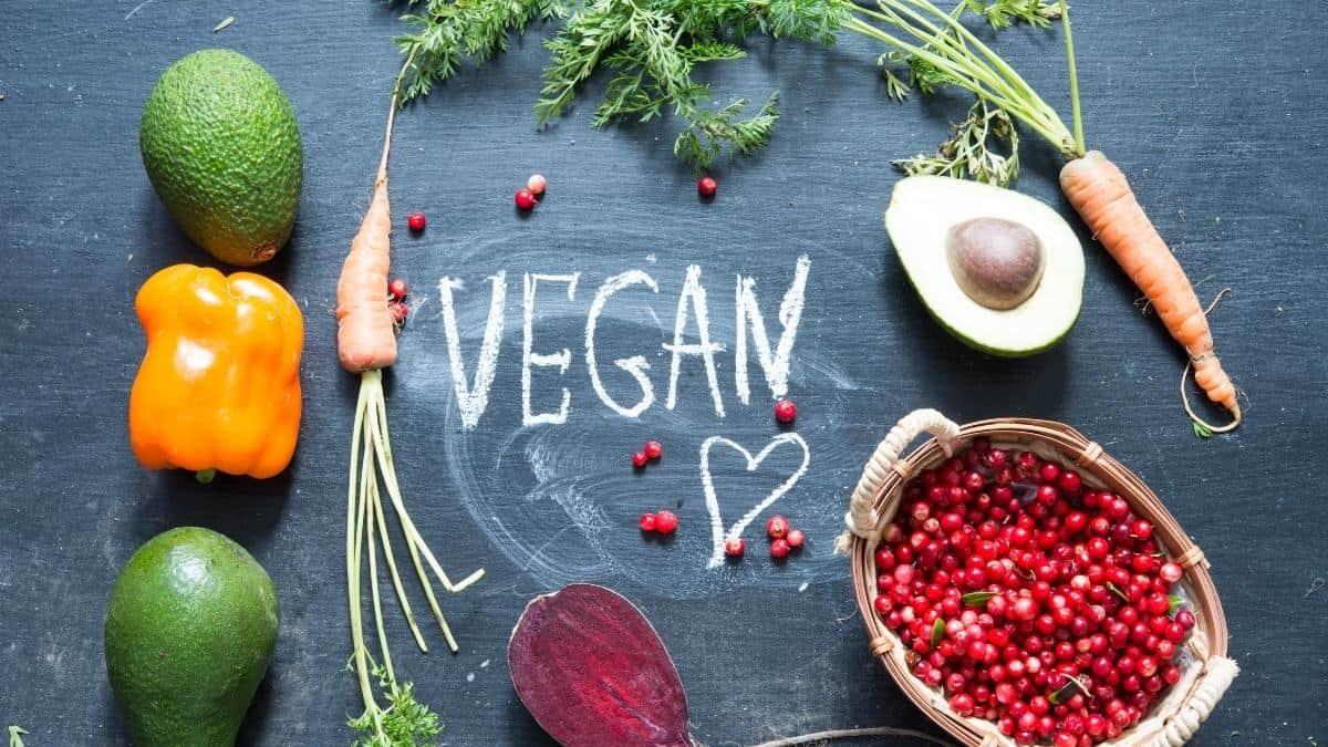 Vegan written on a chalkboard with veggies around it.
