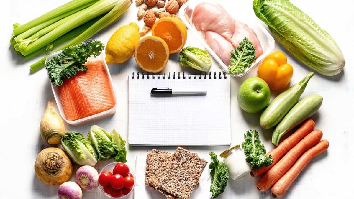 Meal planning notebook surrounded by healthy foods.