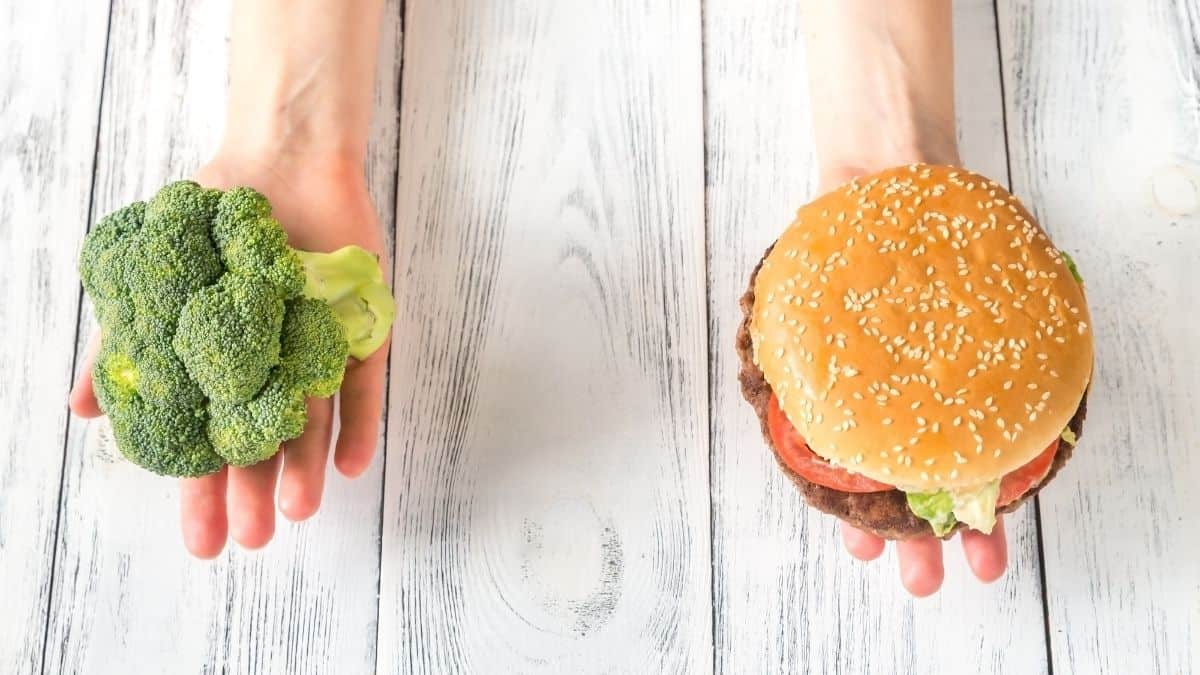 One hand holding a head of broccoli and one hand holding a burger over a wooden surface.