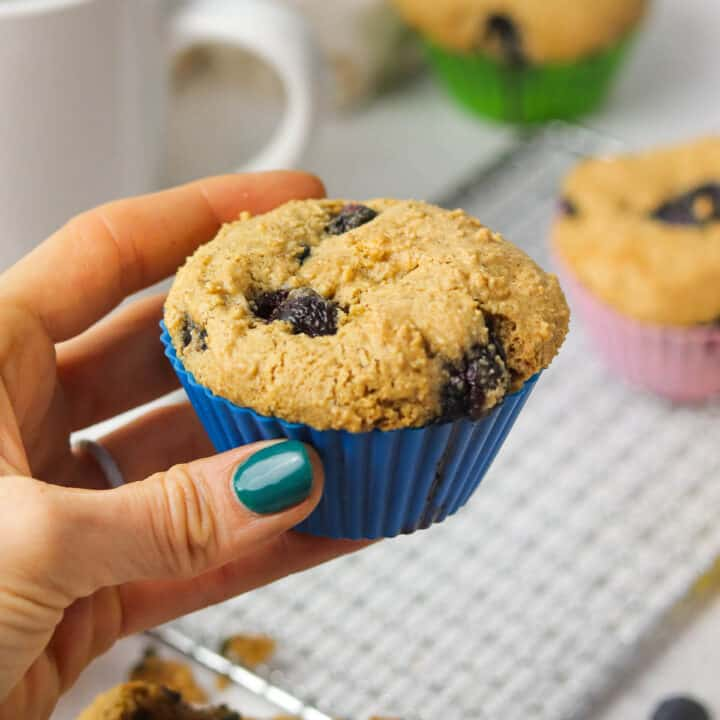 holding a gluten free blueberry muffin.