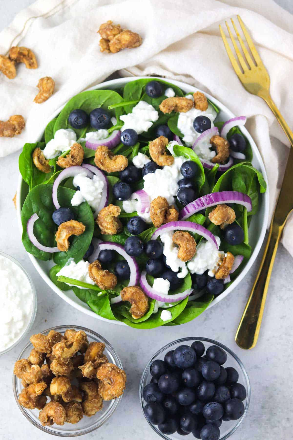 spinach blueberry salad with candied cashews on the counter.