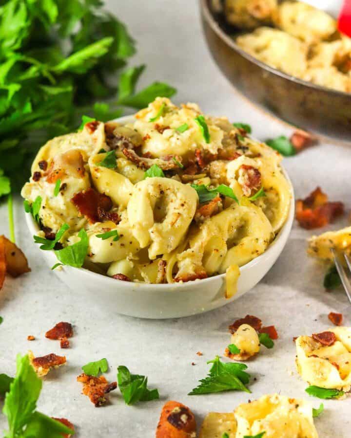 Side angle shot of tortellini carbonara pasta.
