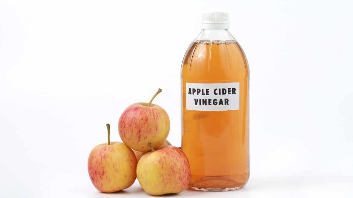 bottle of apple cider vinegar on white background with 4 apples.