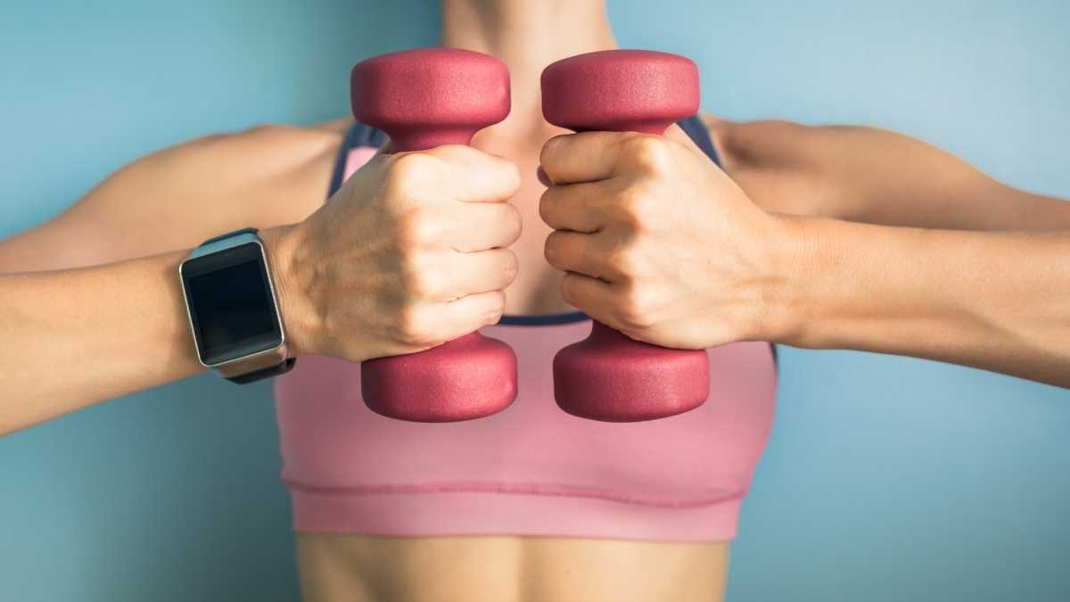 Woman in a pink sports bra holding pink dumbbells.