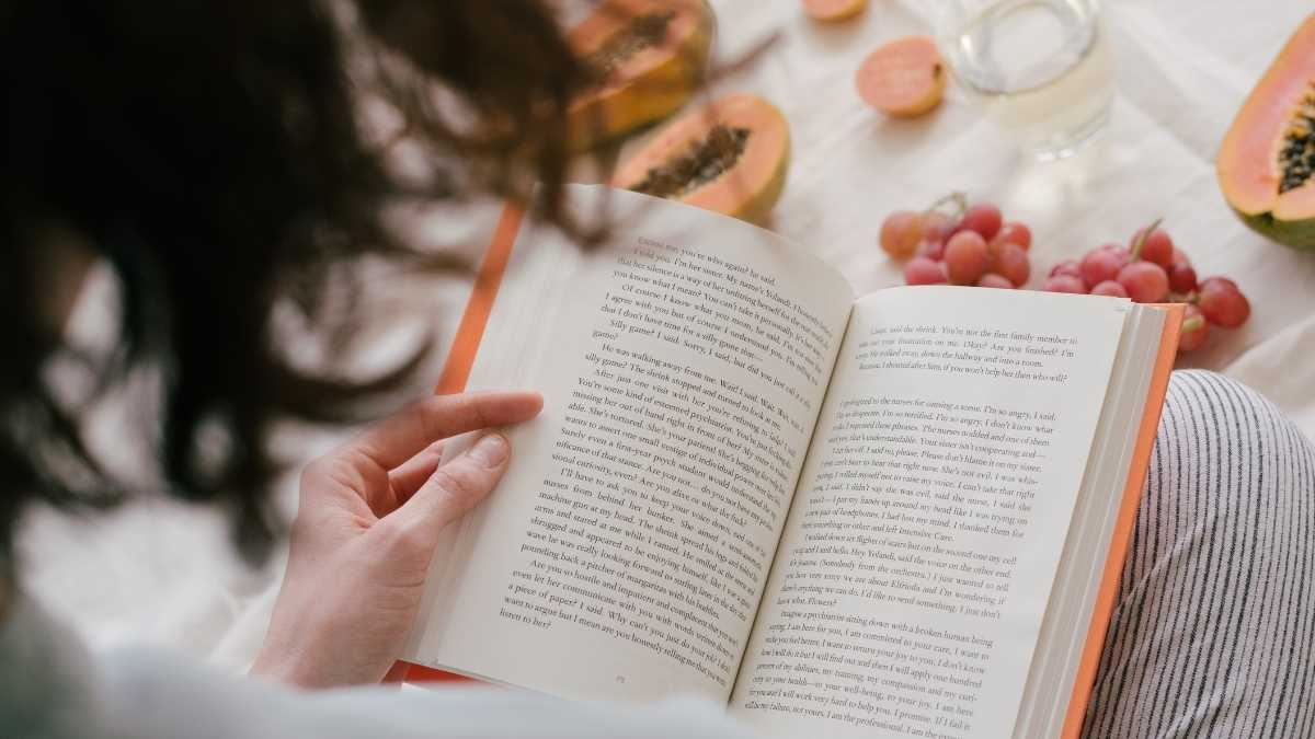 Woman reading a book with fruit in the background.