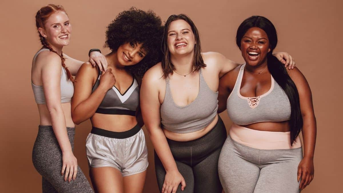 Women of varying body sizes looking happy in sports bras.
