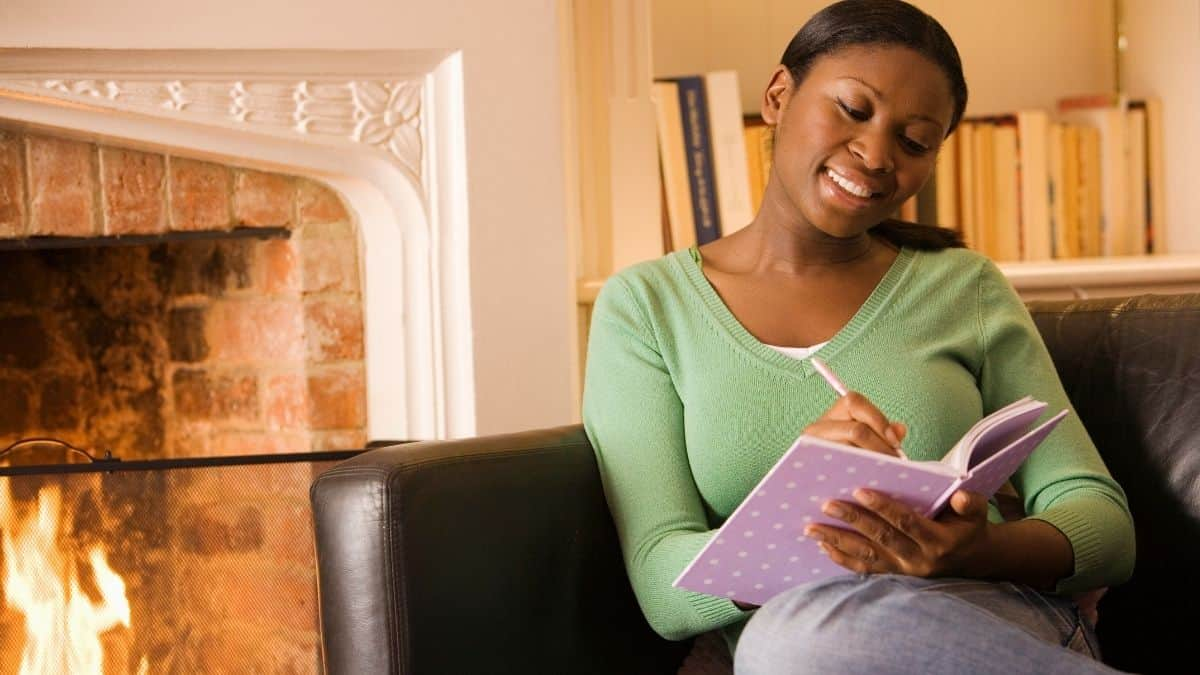 Woman looking happy sitting on the couch writing in a purple journal.