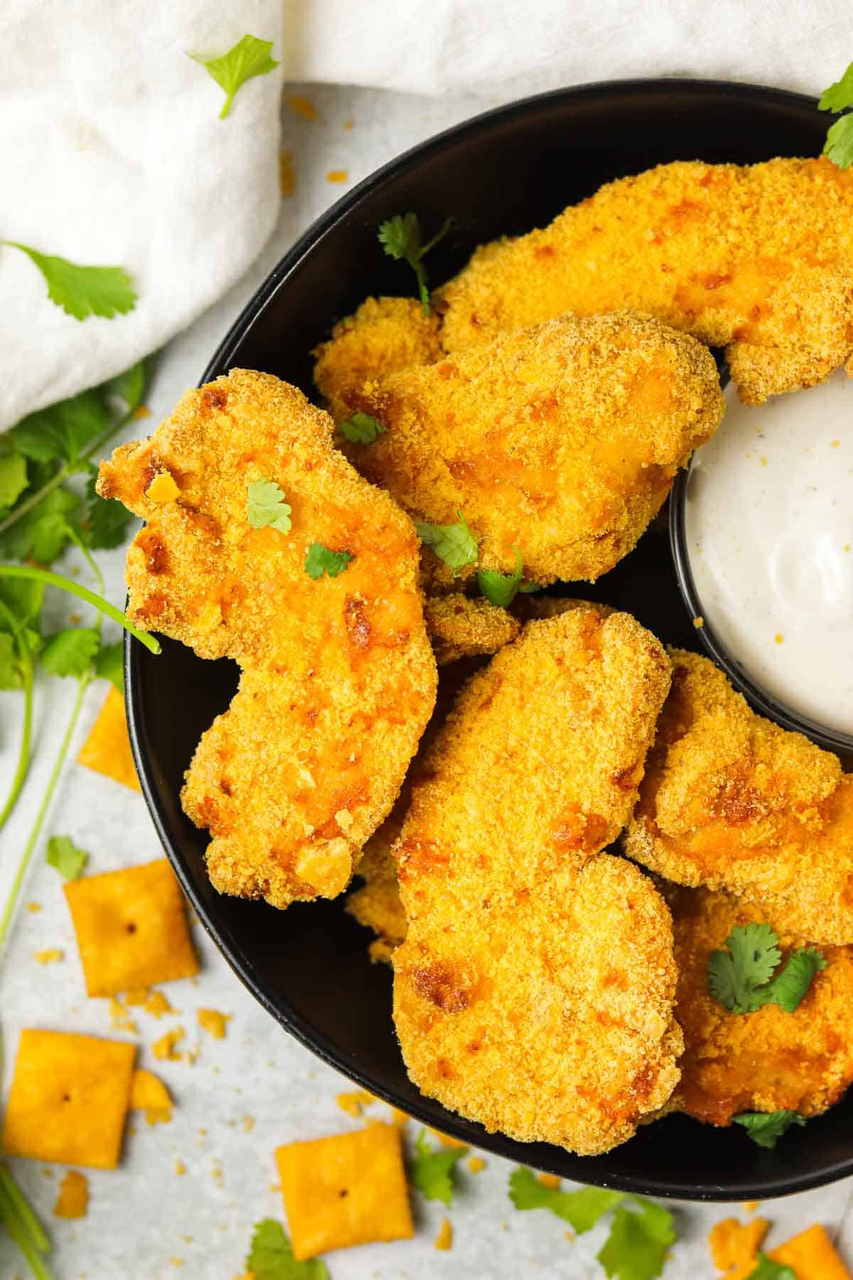 bowl of Cheez It chicken Tenders with ranch and herbs.