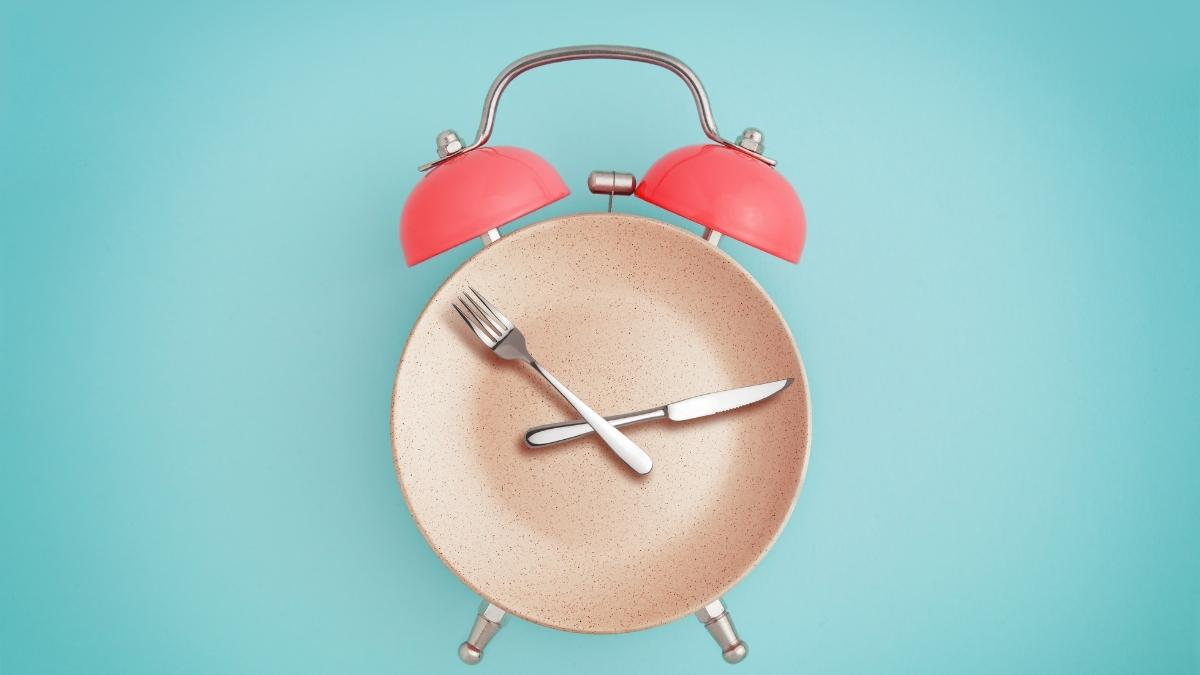plate, fork and knife laid out like a clock on a blue background.