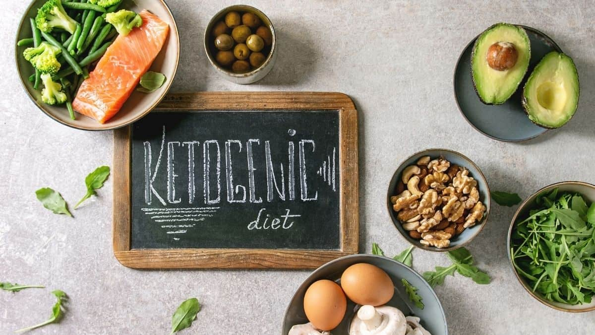 Ketogenic diet written on a chalkboard surrounded by higher fat foods.